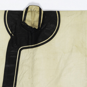 Short flaring jacket with long sleeves, rounded neckline and asymmetrical closure. Sewn of white cotton decorated with wide bands of lacquered black silk at the sleeve, neck and front opening edges; with large frogs of same fabric. Matching trousers with broad short legs, with a band of coarser cotton around the waist.