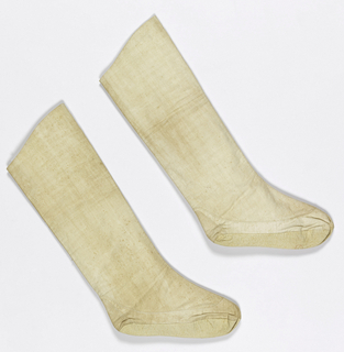 Pair of white cotton bootees made from double thickness of fabric with curved top, seamed down front and back, with quilted sole and heel guard.