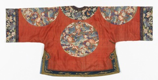 Short coat of of orange-red silk twill, with large medallions on the front, back and on each sleeve, and sleevebands, in polychrome Kesi tapestry wtih some painted lines and shading. Borders of blue-gold kesi around neck and side opening, hem and sleeves. Lined with light blue peony-patterened damask. Medallions contain many symbols: dragons, lotus, fish, sacred vase, the endless knot, etc.