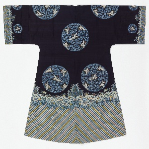 A  robe of dark blue silk with a deep wave border at the bottom and sleeve hems. Tapestry-woven design of eight large circular medallions showing five white cranes with red crests and blue cloud bands. Lined with light blue silk.