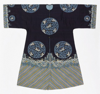 A  robe of dark blue silk with a deep wave boder at the bottom and sleeve hems. Tapestry-woven design of eight large circular medallions showing five white cranes with red crests and blue cloud bands. Lined with light blue silk.