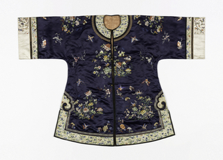 Short coat of dark blue silk satin, embroidered with clusters of flowers and butterflies in multicolored silks. Neckband, sleeve bands and bottom border are of white satin with floral embroidery, edged with black satin. Lined with pale orange silk.