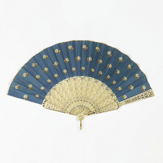 Folding fan with ivory sticks carved à jour with decoration in silver and gilt. Silk leaf with small, repeated flower pattern embroidered in white, yellow, and brown on a blue ground; the reverse is plain white silk.