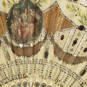 Gauze leaf applied  with satin and lace. Obverse has satin medallion of a female figure with a lyre in classical dress attended by two cherubs. Decorative motifs are in spangles, lace net and embroidery. Guards are pierced steel. Blade are ivory piquéd with steel ornaments.