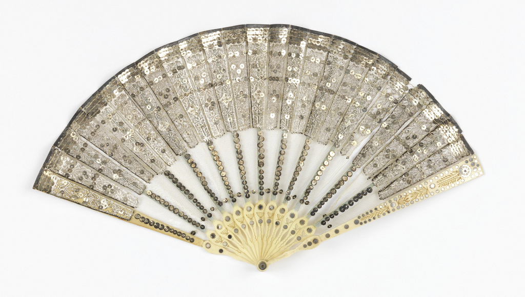 Folding fan with carved ivory sticks inlaid with steel spangles. Leaf is silver cut paper backed with silk gauze and silk tulle, and ornamented with silver sequins.
