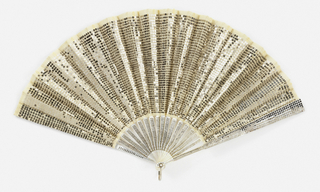 "Pleated fan. White silk mousseline de soie leaf embroidered all over with small steel sequins. Mother-of-pearl sticks inlaid with small round steel piqué work. Guards have inlaid steel piqué decoration of graduated size. In white satin box marked ""Tiffany & Co."""
