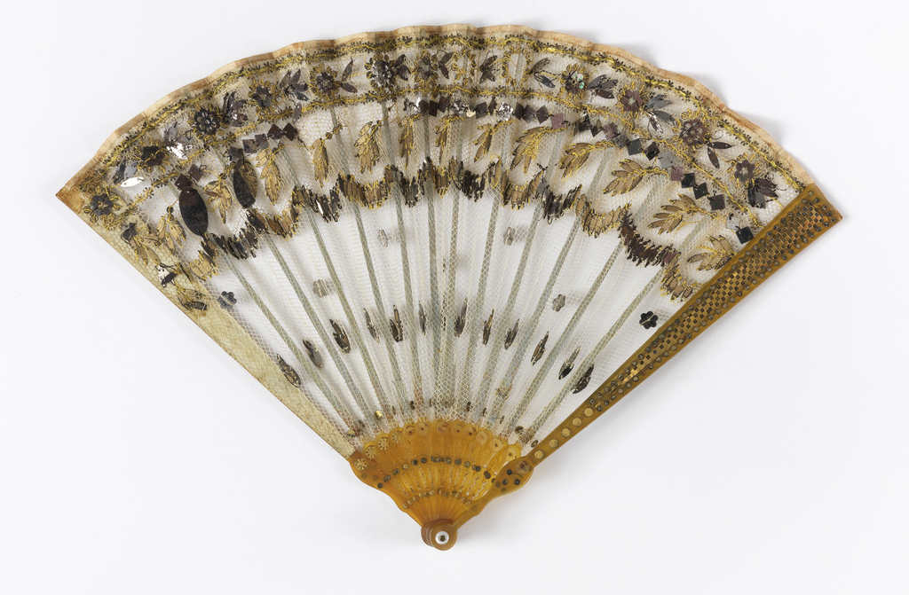 Pleated fan. Leaf is a single layer of white net, obverse appliquéd with gilt spangles and mirror-like steel in varied shapes. Guards and sticks of amber colored horn, pierced and decorated with gilt piqués.