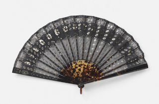 Pleated fan. Leaf of black mousseline de soie; obverse applied with scalloped band of same material; decorated with steel sequins of varying shapes arranged in flower shapes, swags and lines. Tortoise shell sticks and bail.
