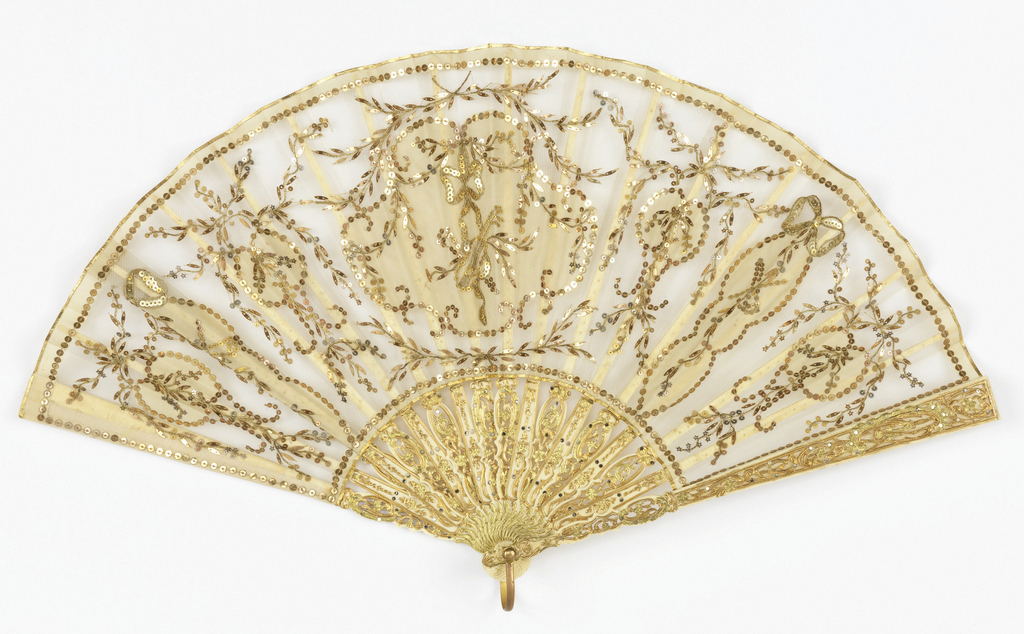 Pleated fan. Leaf of egg-shell mousseline de soie; obverse applied with seven medallions of same materials; embroidered with gold thread, and gilt and silver sequins outlining medallions and forming designs of wheat stalks, ribbons, bows, festoons and musical trophies; guards and sticks of pierced ivory or bone, carved and painted. Gilt metal bail.