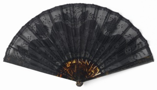 Pleated fan with double leaf. Obverse: black silk net with black silk and black metallic spangles in a variety of shapes. Reverse: silk net. Imitation tortoise shell sticks, with black metallic circles, painted black wooden slips and imitation tortoise shell washer at the rivet.