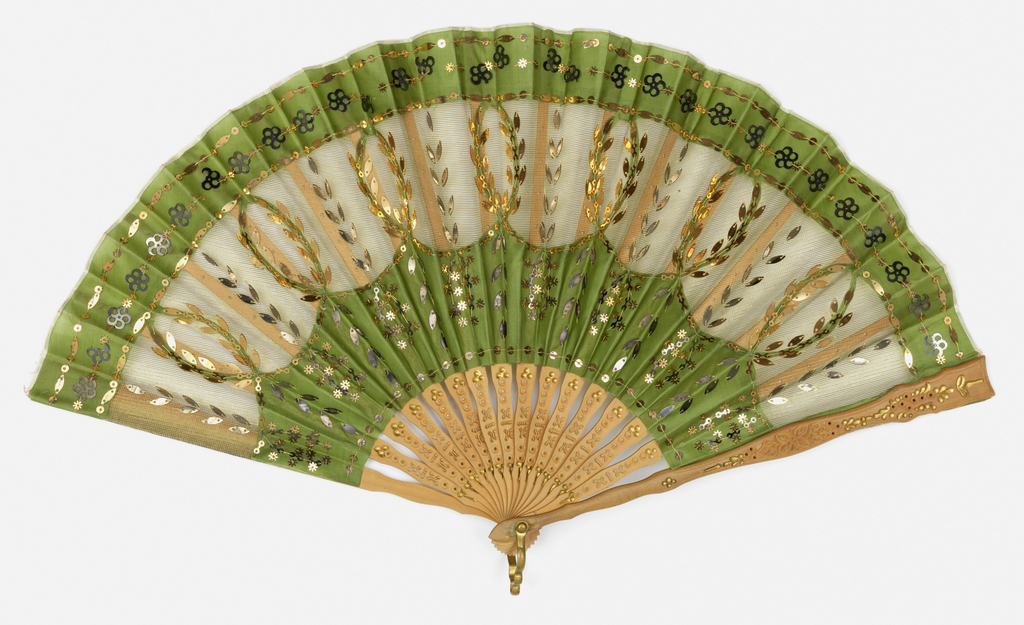 Pleated fan with double leaf. Obverse: leaf of green silk net with appliquéd green silk and gold metallic spangles in a variety of shapes. Reverse: green net leaf. Sticks: drilled light wood with gold painted decoration, metal bail ring at the rivet.