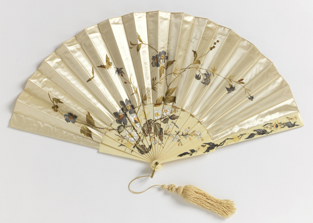 Pleated fan. Printed cream-colored silk leaf showing butterflies and flowers. Ivory sticks with metal foil decoration. Gilt metal bail with cream-colored silk tassel.