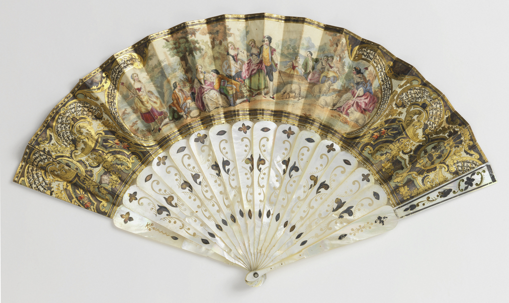 Pleated fan. Printed leaf showing a large central cartouche containing a pastoral scene, surrounded by large gilded scrolls. Carved and pierced mother-of-pearl with metallic foil. Faceted stone at rivet.