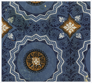 Square of paper showing two motifs of a large-scale geometric pattern. One motif in orange, circular, with repeating blue-black cone shapes, a white design at center and blue-black radial surround. The other motif diamond-shaped.