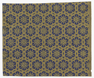 All-over pattern of stylized hexagonal rosettes separated by stylized leaves and dots in a continuous hexagonal design. Blue and yellow on brown.