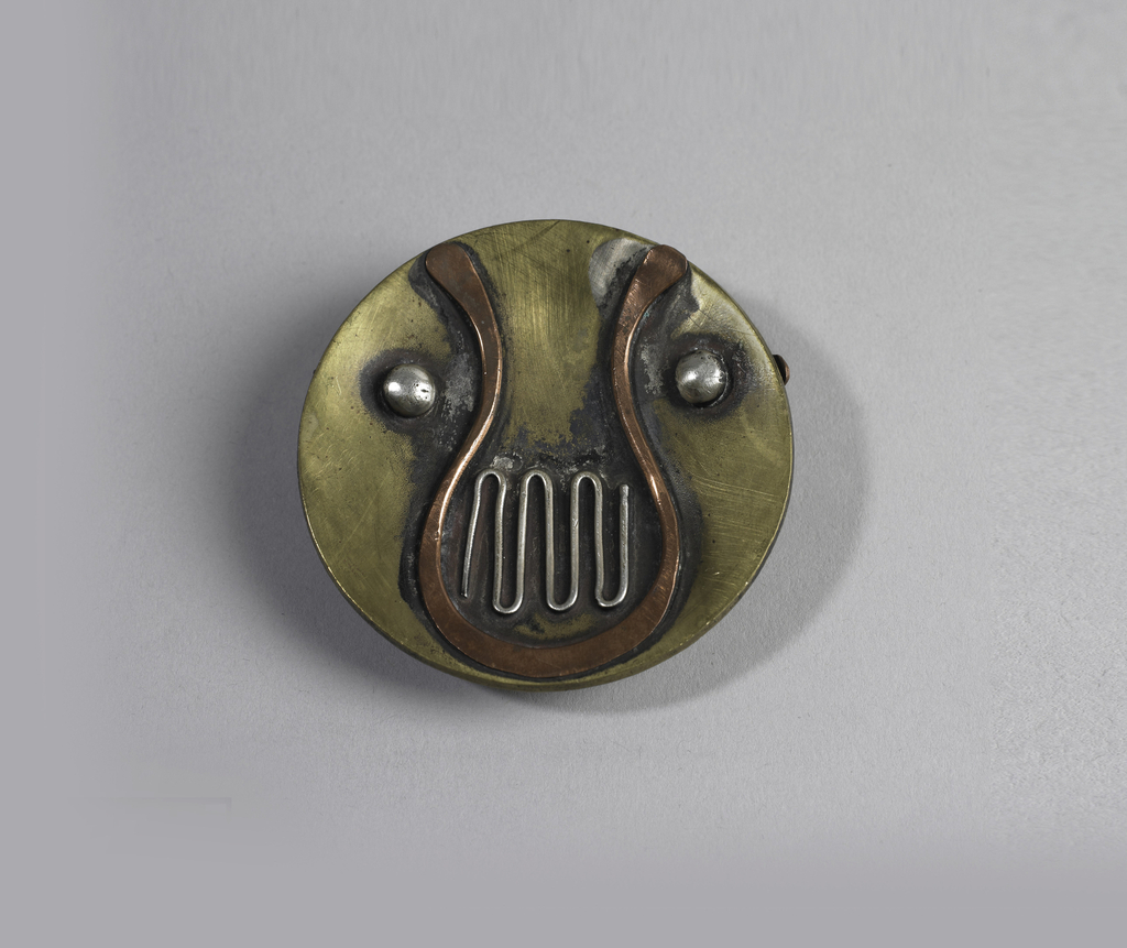 Slightly concave brass disc with silver and copper wire in abstract design,and two silver dots; belt slide on reverse.