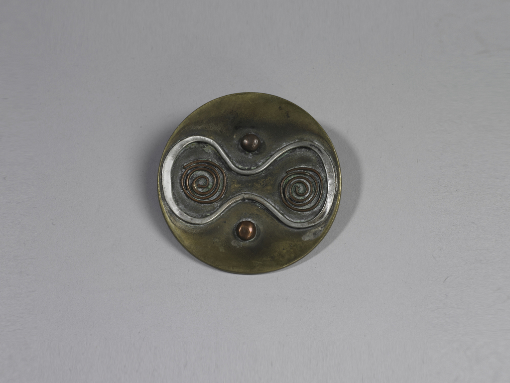 Brass disc with silver wire shape enclosing two copper wire spirals; two copper dots flanking pinched center of silver wire.