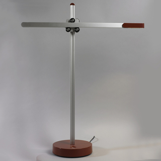 Linear form, reminiscent of a construction crane, composed of a horizontal arm containing an LED array on one end, mounted via a roller mechanism on a vertical post surmounting a circular red base. Horizontal arm can move along three axes: up/down, back/forth, and rotationally. Vertical, red counter-balance mounted on back of vertical post.