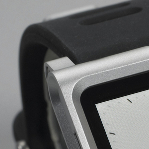 Form composed of simple square frame that accommodates a 6th generation Apple iPod to snap in when being used as watch face and snap out when used as a media player; simple black silicone rubber strap with metal buckle.
