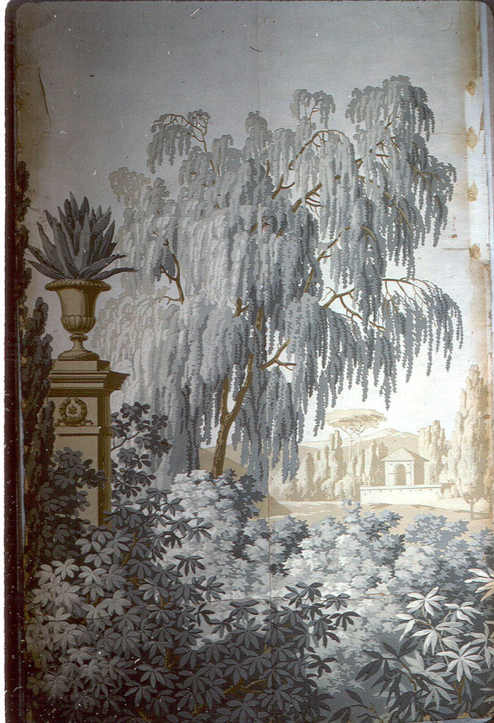 At left, a high pedestal supporting an urn in which grows a cactus-like plant with large leaves. Leafy foliage and trees. Small building with surrounding terrace, at right, background. Printed in grisaille and brown.