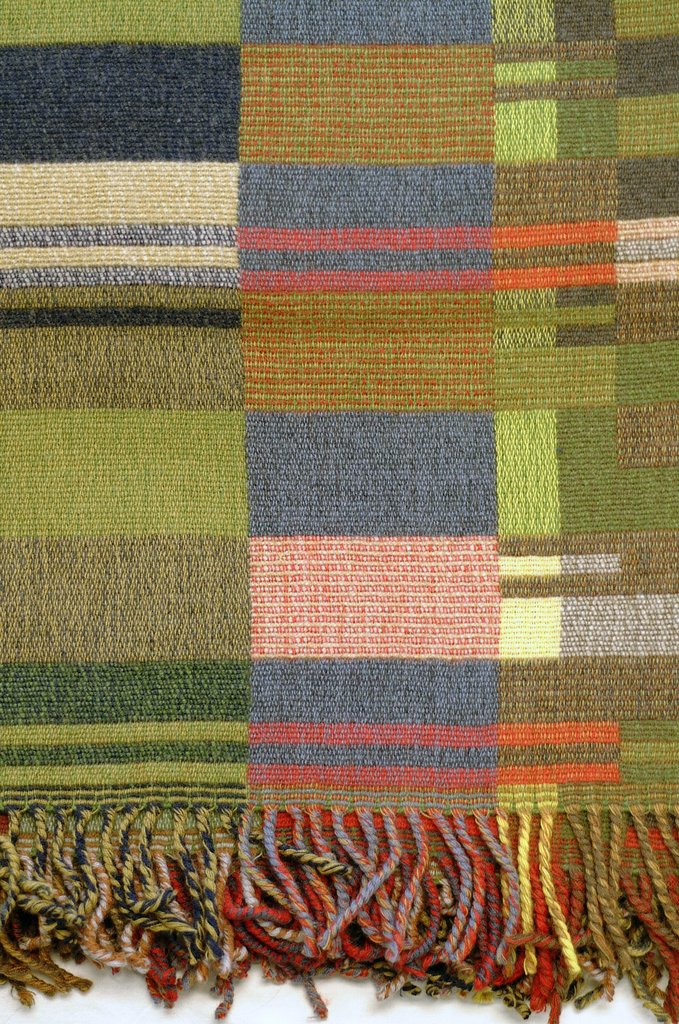 Lambswool blanket with twisted fringe on the warp ends. Abstract composition of vertical columns of rectangles and bands in mixed shades of grays, browns, blues, and greens with touches of yellow and red.