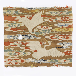 Most of a Ming dynasty Sixth Rank square showing a pair of egrets with spread wings arched across a gold sky filled with brightly colored attenuated cloud streamers. Birds are white with the characteristic slender head plume, yellow beak, feet and eyes, with pale green details. Cloud bands are white with shades of blue, pale green, yellow and vermillion on a gold metallic ground.