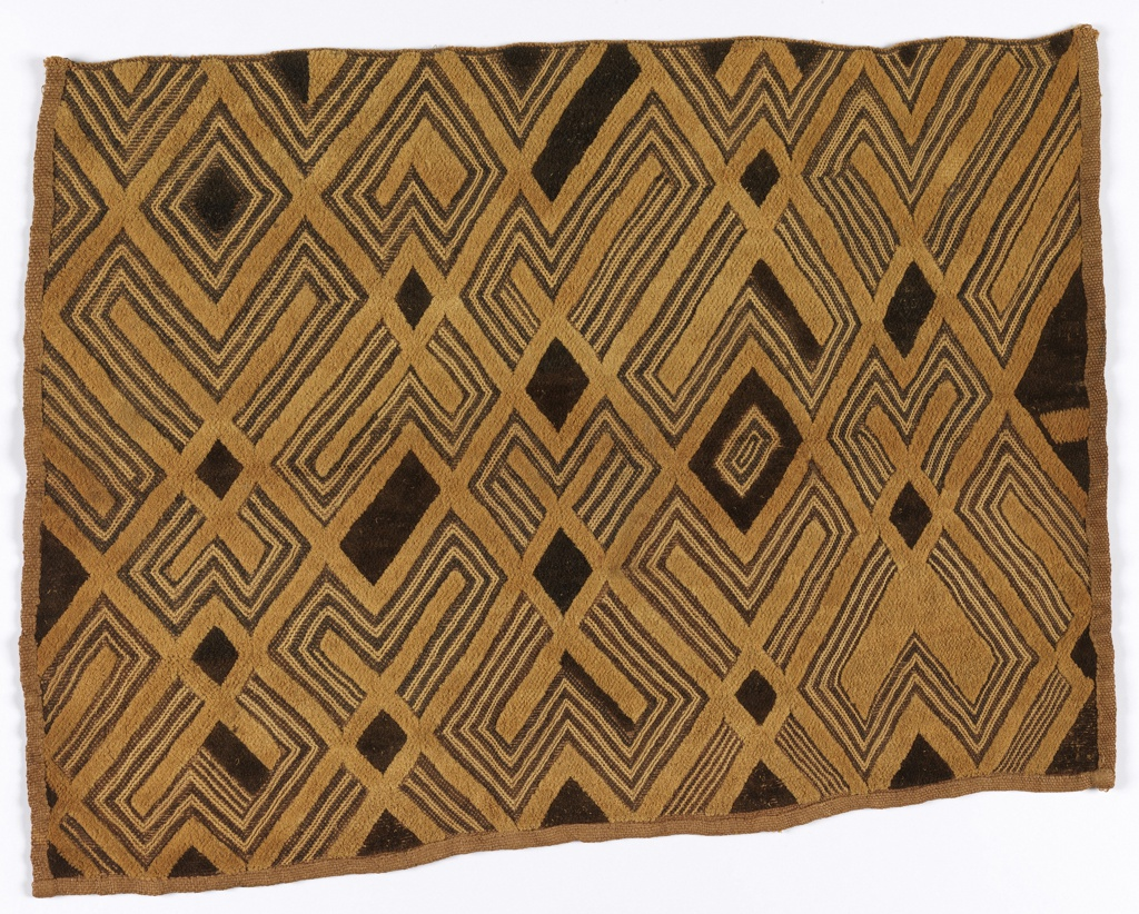 Status cloth with a complex geometric pattern of diamonds and crosses, composed of bands of striped natural and dark brown stem stitch, and areas of natural and dark brown embroidered pile.