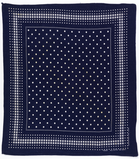 Square bandana with a deep blue ground and a field of white dots; border with small and large white dots.