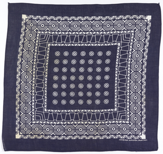 Square bandana with a deep blue ground, field of white concentric circles, and a deep border of concentric circles, half-circles alternating direction, and trapeziods.