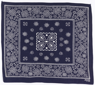 Square bandana with a blue ground and design in white. Square center medallion with four-lobed foliate design, surrounded by snowflakes and leaves. Deep border of scattered snowflakes, leaves, and smaller versions of the center medallion.