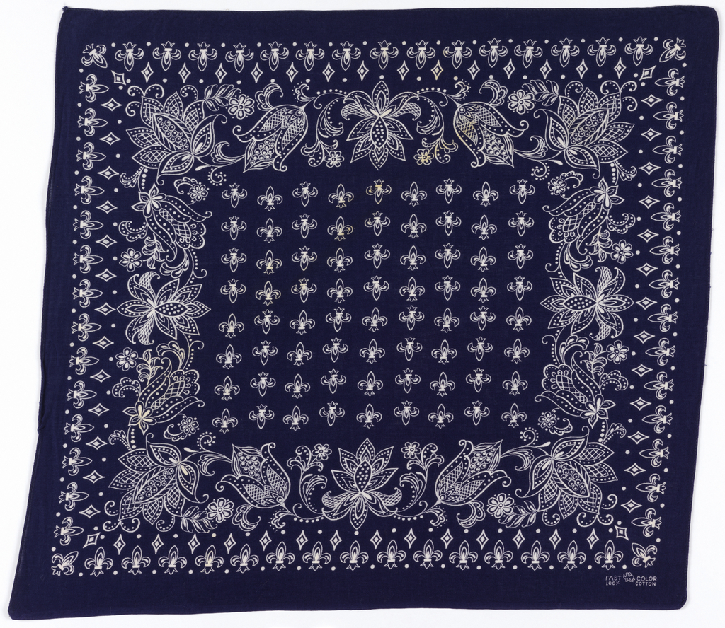 Square bandana with a deep blue ground and design in white. Deep floral border surrounding field of fleurs de lys. Narrow outer border of fleurs de lys.