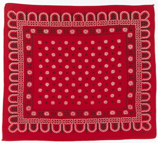 Square bandana with a red ground and design in black and white. Field of black and white stars, two narrow boders of stars, and a wide lace-like scalloped border.