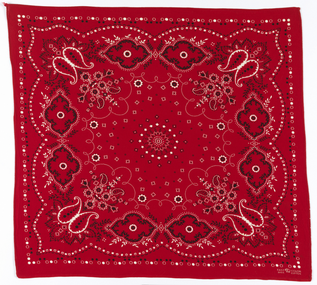 Square bandana with a red ground and design in black and white. Circular center medallion surrounded by small diamond forms. Deep shaped foliate border. Narrow outer border of small circles.