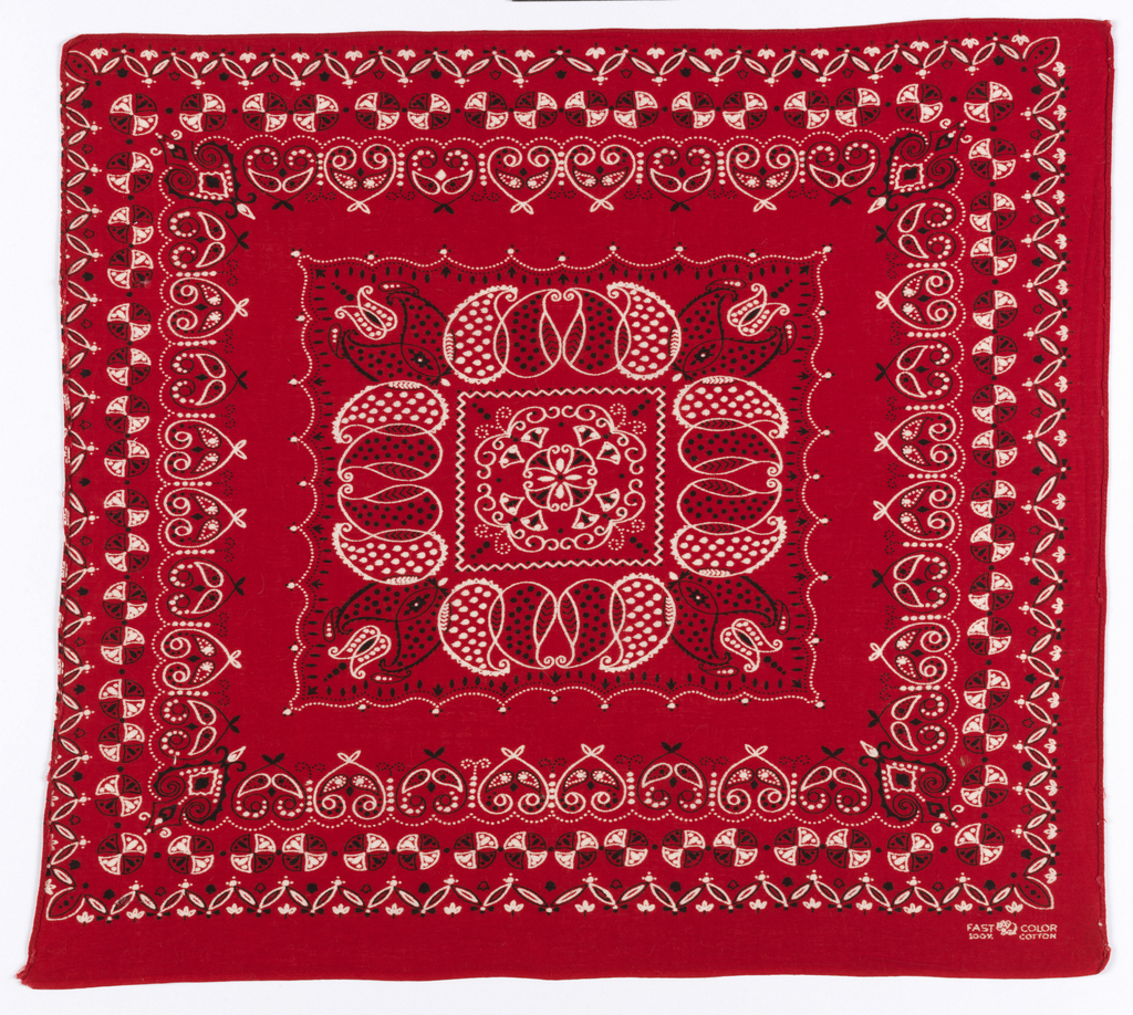Square bandana with red ground and design in black and white. Square center field with paisley forms, surrounded by boders of hearts and circles, all with decorative infillings.