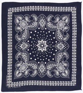 Square bandana with deep blue ground and design in white. Eight-pointed star in the center surrounded by dots of increasing size. Elaborately scrolled border with floral and paisley forms with decorative infillings. Narrow outer border of paisely forms.