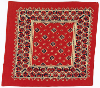 Square bandana with a red ground and design in black and off-white. Field of off-set diamonds interspersed with small oval medallions. Border of interlocking fan-like shapes.