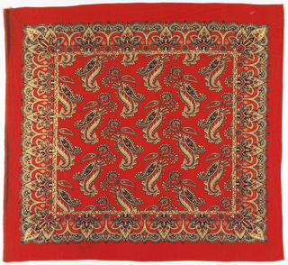 Square bandana with red ground and design in black and off-white. Field of large paisley shapes facing in alternate directions. Border of decorated trefoils.
