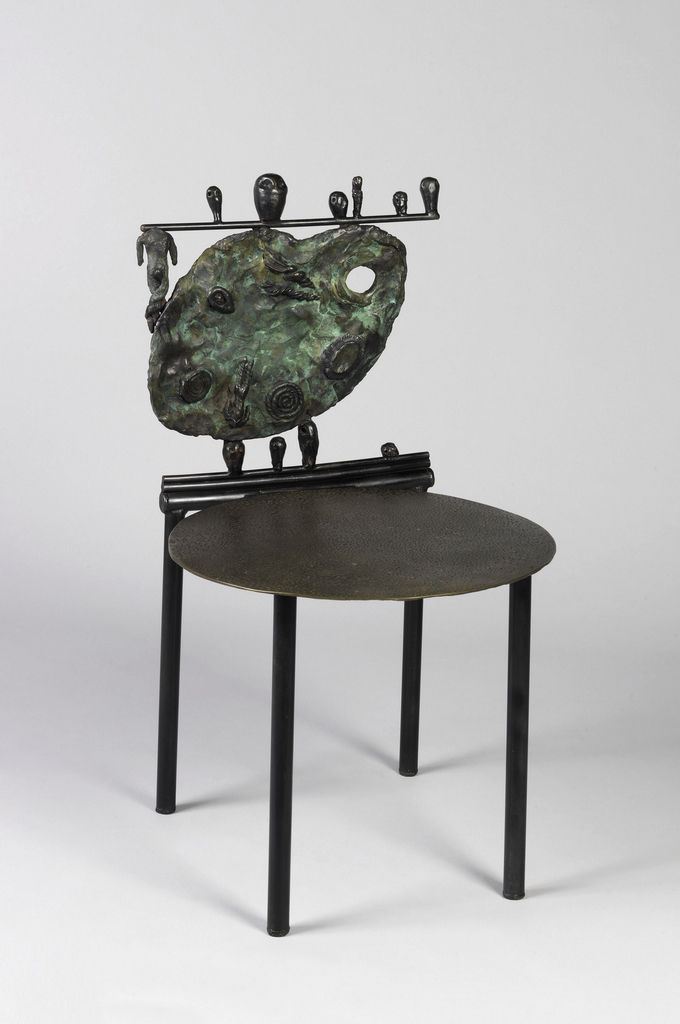 """Flat disk seat on four straight cylindrical legs; back composed of cast bronze painter's palette decorated with spirals; """"crest rail"""" consisting of a horizontal rod, a headless figure below the rod, to left of palette, and six different sized heads sitting on the rod; three cast bronze heads situated between the seat and back, supporting the back, with a fourth head to the right."""