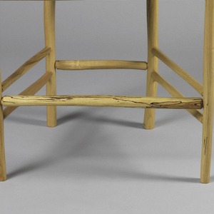 Upholstered seat in cream; back composed of two thick wooden posts with one cross band at the top and one at bottom; and two thinner posts of wood filling in the splat. Straight legs with one stretcher in both front and back and two at each side.