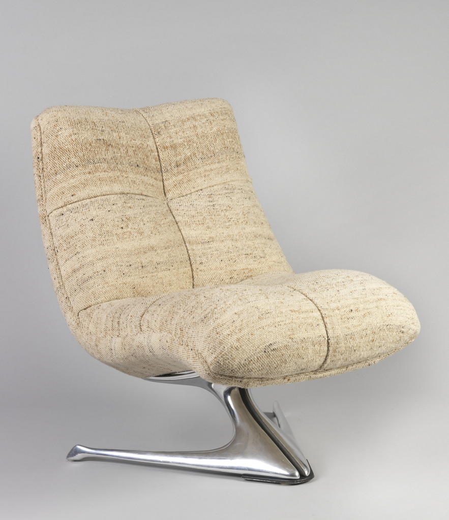 L-shaped cushioned chair in speckled cream and brown; resting on V-shaped chrome stand.