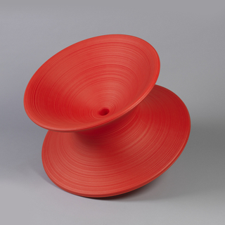 Short red contoured cylindrical form reminiscent of a child's toy top; shallow bowl-shaped seat; pointed base, causing form to sit at an angle.