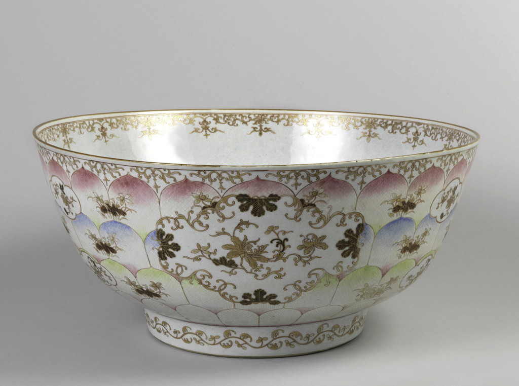 Deep round bowl on high foot. Pale blue ground flecked with umber. Centered with lotus plants in aubergine and gold penciled with red; outer walls have four rows of etched and colored lotus petals, and scrolled medallions.