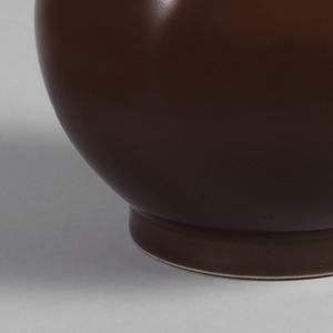 Bottle-form: globular, with straight slender neck, short foot. Coated from white rim to foot with monochrome oxblood color glaze of pear skin texture.