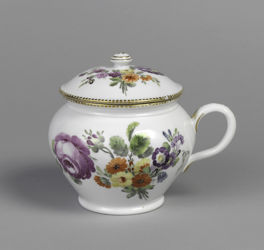 Bulbous jug with loop handle and lid with button finial. Jug and lid have gilt rim, and both decorated with purple and orange blossoms, and green leaves and stems on white background.