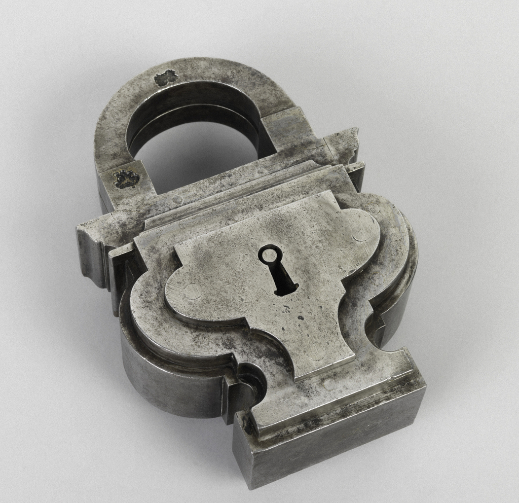 (a) Padlock in the shape of a footed urn with stepped levels, and arced shackle, with two unidentifiable marks.