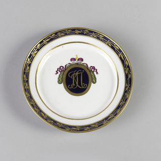 Dessert plate with gold monogram of Konstantin Pavlovich in blue oval, framed with gold and crested by purple crown and green wreath. Gold laurel on blue band around edge.