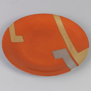 Circular plate with red-orange enamel ground featuring geometric decoration of two wide L-shaped gilded bands and one wide L-shaped platinum band. Plain white glaze on reverse. (One of a set of 12 plates. 1969-97-14a/l.)
