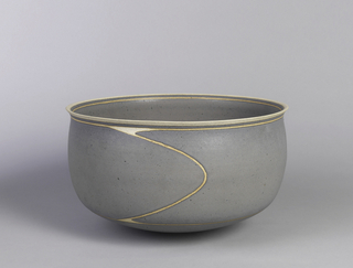 Deep bowl with slightly curved sides, in grayish-blue with a line that circles below edge of mouth and leads to lower part of bowl near base.