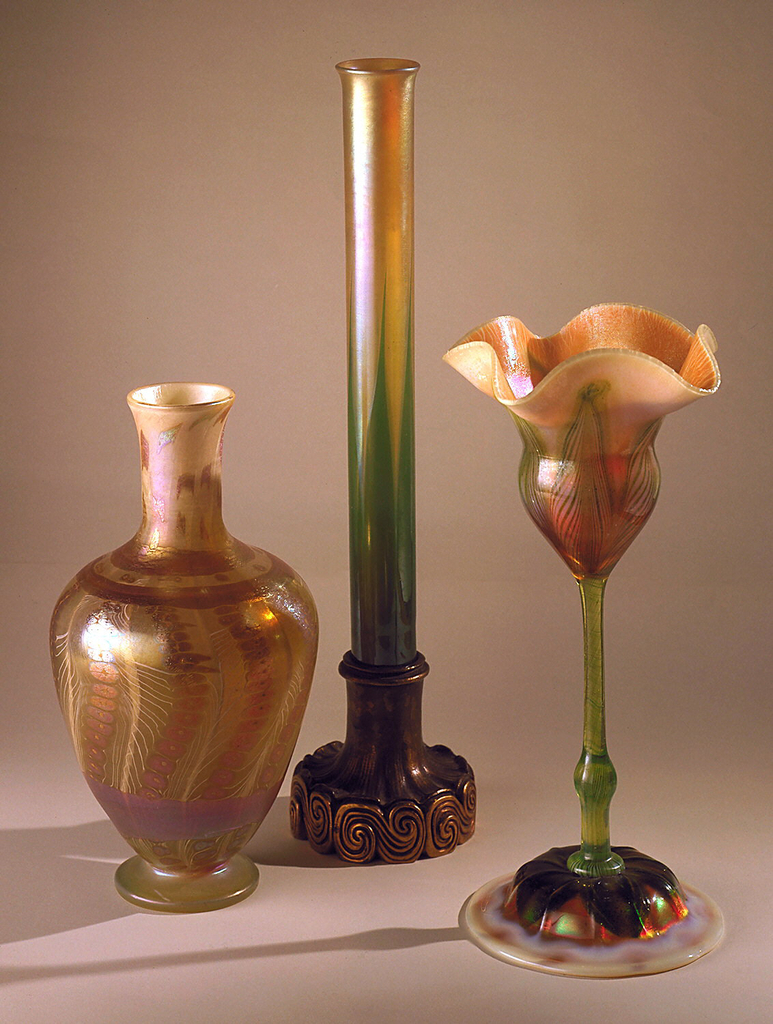 Tall, cylindrical glass vase (a) with slightly flared mouth; dark green leaf motif at bottom eased over gold favrile glass.  Vase fits into socket of bronze base (b) patinated at top, inverted trumpet-shaped, ruffled, resting on series of horizontal S-curves picked out with gilding.  Three metal 3-pronged holders (c,d,e) to fit into base to hold vase.