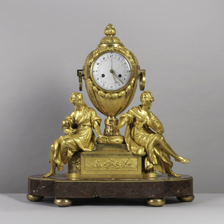 Large bronze clock; center part made up of large vase with round ring handles; acanthus and laurel leaves. Dial painted with small flowers on white enamel. On each side of the vase is a female figure; one holding a terrestrial glob (Geography), the other holding a scroll (Literature). The plinth on which the two figures are seated is decorated with chiseled plaques in front showing cupids and decorative motifs. The clock sits on a large red marble stand.